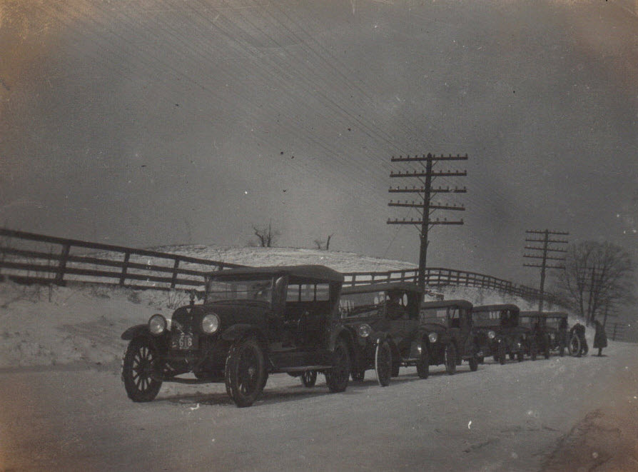 Line of dealer cars on snowy road