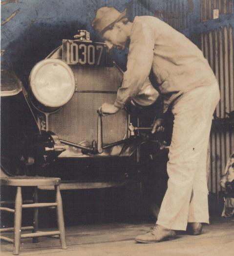 Rockville Garage mechanic hand cranking old car