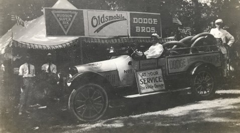 1918 - Hudson Super Six, Oldsmobile, and Dodge Brothers Motor Cars on display. Lewis Reed in drivers seat.