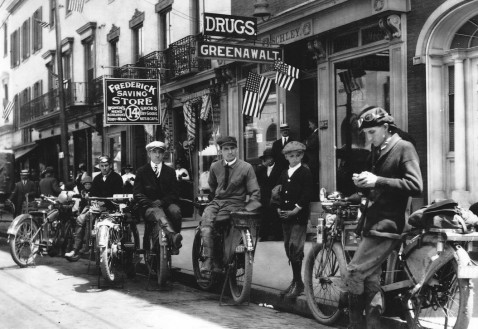 Lewis Reed taking photograph (from left: Lewis Reed's motorcycle, Edgar Reed, unknown person, Bernard Hanshaw, unknown child, unknown man) in front of Greenawalt Drug Store on Market Street in Frederick, MD circa 1915