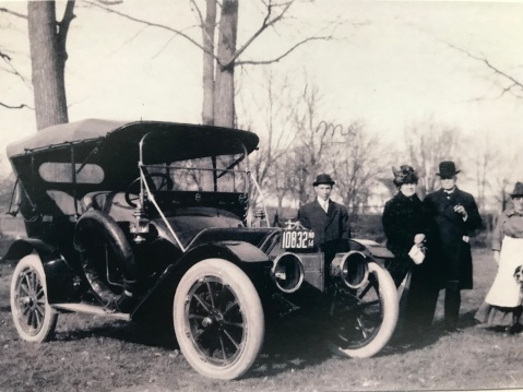 Chauffeur Lewis Reed (left) with unidentified family, 1914