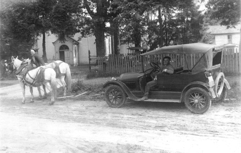 horses towing old car