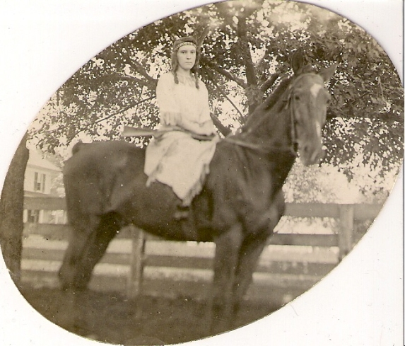 woman holding rifle on horse