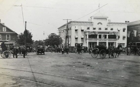 early 20th century street scene with horses and cars